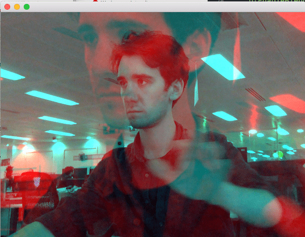 Struan appears with a blue hue in an office. A larger image with a red hue appears super imposed over the original image. Struan is waving.
