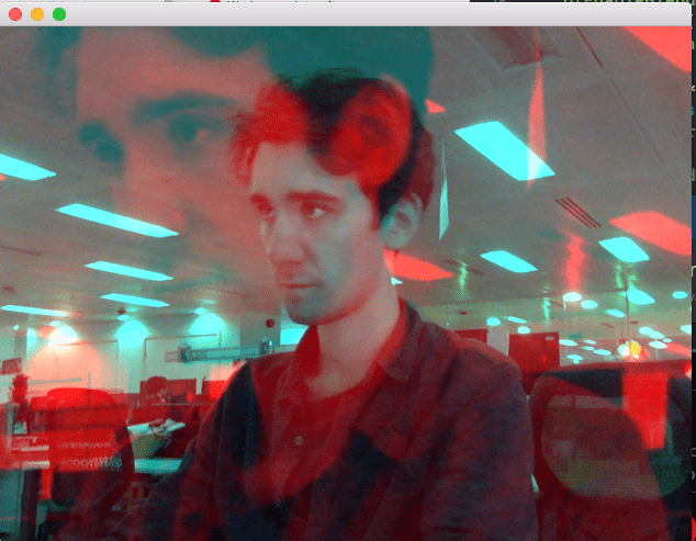 Struan appears with a blue hue in an office. A larger image with a red hue appears super imposed over the original image. Struan is looking pensive.
